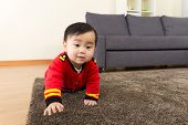 Baby boy creeping on carpet