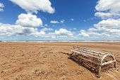 Broken lobster trap rests on an empty Prince Edward Island beach.