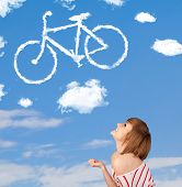 Young casual girl looking at bicycle clouds on blue sky