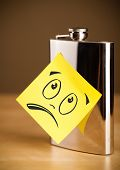Drawn smiley face on a note stuck on a hip flask