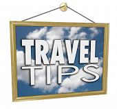 Travel Tips words on a hanging sign with clouds in blue sky advertising helpful tips, advice and inf