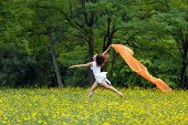 Agile barefoot woman with curly brown hair leaping in the air in a meadow of yellow wildflowers trailing a colorful orange scarf in the breeze as she celebrates her freedom and the beauty of nature