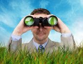 Businessman hiding in the long grass looking through binoculars searching for answers concept for bu