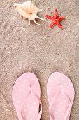 Color flip-flops on sand background