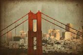 Golden Gate Bridge closeup with San Francisco downtown at sunset.