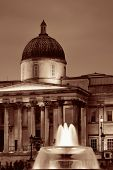 Trafalgar Square at night with fountain and national gallery in London
