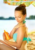 foto of sun-tanned  - Suntan Lotion Woman Applying Sunscreen Solar Cream - JPG
