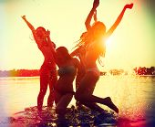 Beach Party. Teenage girls having fun in water. Group of happy young people dancing at the beach on