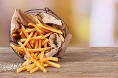 Tasty french fries in metal basket on wooden table, on light background