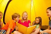 Five kids read books in a tent