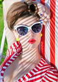 Colorful summer portrait of young attractive woman wearing sunglasses lying down on a deck chair in