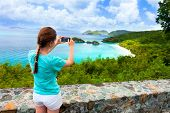 Back view of tourist girl taking photo with mobile cell phone of Trunk bay on St John island, US Vir