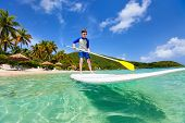 Little boy on tropical beach vacation paddling on stand up board