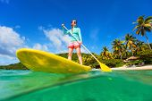 Split underwater photo of young active woman on tropical beach vacation paddling on stand up board