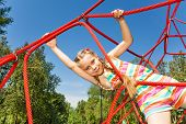 Girl with two braids hangs on ropes of red net