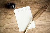 stock photo of inkpot  - goose quill on empty paper and inkpot on wooden table - JPG
