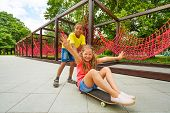 Boy pushing girl sitting on skateboard and roll