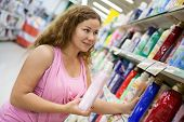 Young Caucasian Woman Holding Cleaning Detergent In Shop