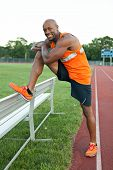 stock photo of hamstring  - African American man in his 30s stretching out before a run at a sports track outdoors - JPG