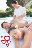 Attractive couple enjoying couples massage poolside against pink hearts