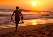 Surfer walking with the board along sandy beach at sunset