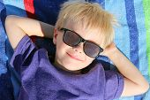 picture of children beach  - A happy young child is relaxing with his hands behind his head on a rainbow striped beach towel while wearing sunglasses on summer vacation - JPG