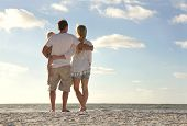 picture of three life  - The backs of a happy family of three people including mother father and baby are standing on a white sand beach looking out at the ocean on a summer vacation - JPG