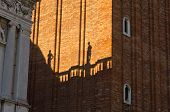Figurine shadows on a Campanila bell tower wall at piazza San Marco in Venice