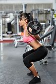 pic of squatting  - Young fitness woman doing barbell squats in a gym - JPG