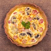 Homemade Quiche Lorraine, backed in a terracotta pie dish, over old wood background