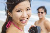 Man & woman Asian couple, boyfriend girlfriend in bikini, taking vacation video or photograph at the beach