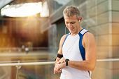 stock photo of mature men  - Portrait Of Happy Mature Man With Heart Rate Monitor On Wrist - JPG