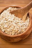 Oat flakes at wooden plate on wooden background