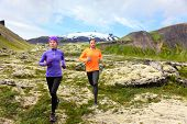 Sport running. Runners on cross country trail outdoors working out for marathon. Fit young fitness model man and asian woman training together outside in mountain nature on Snaefellsnes, Iceland.