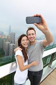 Hong Kong Victoria Peak tourists couple taking selfie photo picture with smartphone enjoying view over Hong Kong and Victoria Harbour. Young happy multiethnic couple traveling in Asia.