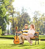 Mature man sitting with his wife in park and holding a guitar shot with a tilt and shift lens