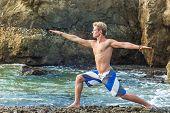 foto of virabhadrasana  - Young man doing yoga and meditating in warrior pose at sea beach - JPG