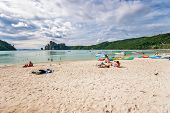 PHI PHI ISLAND, THAILAND- JULY 23, 2007: Tourists sunbathing on sand of Phi Phi island beach. Phi Phi island near the coast of Thailand, between the mainland and Phuket island. Part of Krabi province