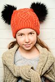 foto of knitted cap  - Cute smiling teenager girl wearing warm knitted sweater and knitted cap - JPG