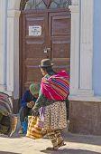 UYUNI, BOLIVIA, MAY 15, 2014:  Local woman in traditional attire walks at Plaza Arce