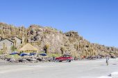 SALAR DE UYUNI, BOLIVIA, MAY 15, 2014:  Vehicle of organized tours waits at Isla Incahuasi while tourists trek and visit