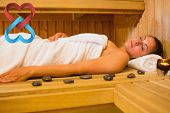Peaceful brunette woman lying in a sauna against linking hearts