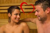 Cheerful couple relaxing in a sauna and chatting against heart