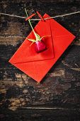 Red  envelop and rose  hanging on the clothesline. On old wood background