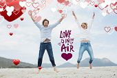 Cheerful young couple jumping at beach against love is in the air