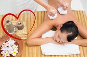 Peaceful brunette enjoying a herbal compress massage against heart