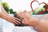 Peaceful man getting a head massage poolside against heart