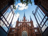 image of gates heaven  - Open metallic gate towards an old Christian church with impressive architecture under a cloudy blue sky concept of salvation heaven and spiritual comfort from low - JPG