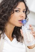 Beautiful young Latina Hispanic woman smiling, relaxing and drinking a bottle of water