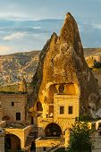 foto of chimney rock  - Hotel rooms cut down in the rock in the light of the setting sun - JPG